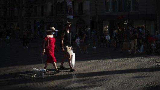 Menschen mit Mundschutz gehen auf den Las Ramblas in Barcelona.
