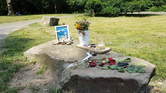 Essen: Ein Foto, Blumen und Kerzen wurden in einem Park abgelegt.