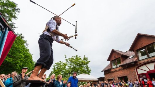 Ein Straßenkünstler vom Chaos Variete jongliert bei der Kulturellen Landpartie im Wendland auf einem Hof mit Fackeln.