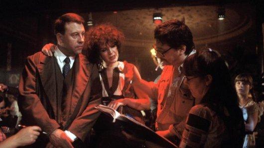 Günter Lamprecht (als Franz Biberkopf, l) und Elisabeth Trissenaar (M) bei einer Besprechung mit dem Regisseur Rainer Werner Fassbinder (2.v.r.) während der Dreharbeiten zu dem Fernsehfilm Berlin Alexanderplatz.
