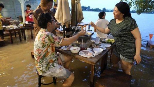 Menschen sitzen trotz des hohen Wasserstands im Chaopraya Antique Café. Das von der Flutkatastrophe betroffene Restaurant hat sich zu einem Hotspot entwickelt.