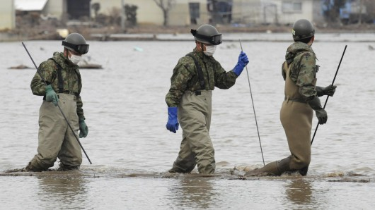 Japan Ground Self-Defense Force personnel wade through a muddy rice paddy as they continue searching for missing people in the area devastated by the March 11 tsunami in Minamisoma, Fukushima Prefecture, Japan, Thursday, April 7, 2011. (AP Photo/Yomiuri Shimbun, Masamine Kawaguchi) JAPAN OUT, MANDATORY CREDIT
