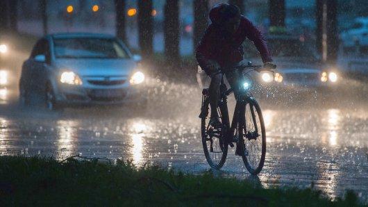 Ein Fahrradfahrer und Autos fahren am 19.07.2017 bei einem Unwetter mit Starkregen auf einer Straße in Hannover (Niedersachsen). Foto: Silas Stein/dpa +++(c) dpa - Bildfunk+++
