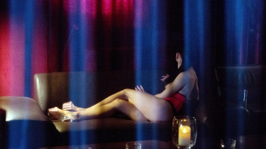 """ARCHIV - ILLUSTRATION: Eine Prostituierte sitzt am 21.10.2013 im Rahmen eines Fototermins auf dem Sofa eines FKK-Clubs. (zu dpa: """"Debatte über Prostituiertenschutzgesetz"""" vom 25.10.2017) Foto: Marijan Murat/dpa +++(c) dpa - Bildfunk+++"""
