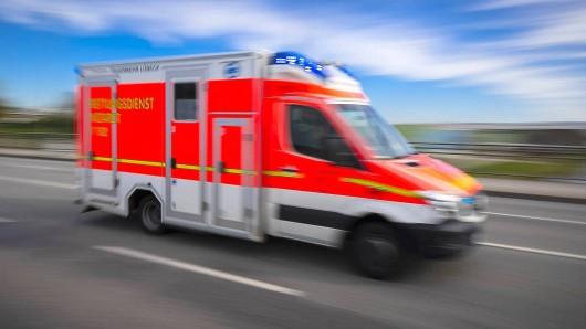 Ein Krankenwagen fährt mit Blaulicht über eine Brücke.