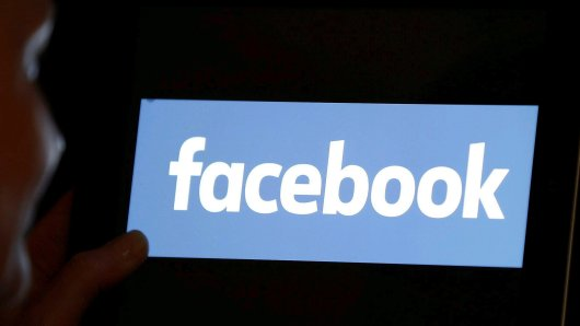 FILE PHOTO: A woman looks at the Facebook logo on an iPad in this photo illustration taken June 3, 2018. REUTERS/Regis Duvignau/Illustration/File Photo