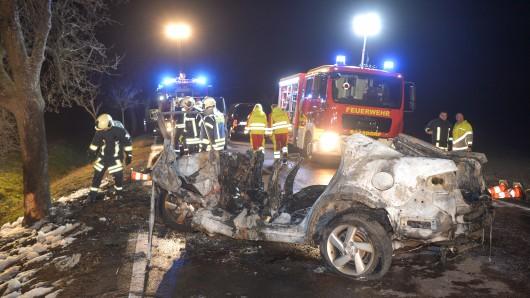 Sachsen-Anhalt, Köthen: Feuerwehrleute und Rettungskräfte stehen auf einer Landstraße hinter einem ausgebrannten Auto. Bei dem Autounfall sind drei Menschen, darunter ein Kind, verbrannt. Ein Säugling wurde aus dem Wrack gerettet.
