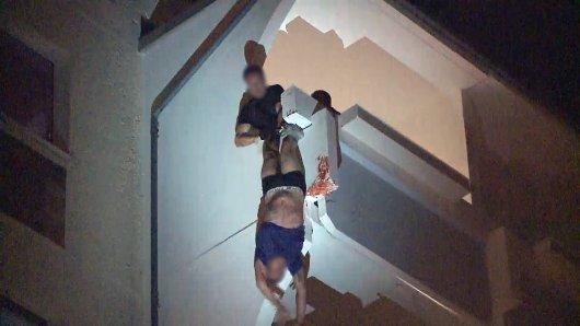 Ein Polizist versucht den Mann noch vor dem Todessturz zu bewahren.