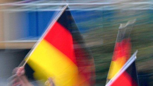 """ARCHIV - 07.09.2018, Sachsen, Chemnitz: Demonstration des rechtspopulistischen Bündnisses Pro Chemnitz: Mit Deutschland-Fahnen ziehen Demonstrationsteilnehmer durch die Innenstadt. Als in Chemnitz alles schon vorbei war, hat er noch den rechten Arm hochgereckt - nun ist im Schnellverfahren ein 33-Jähriger verurteilt worden. Weitere Prozesse werden folgen. (zu dpa """"Bewährungsstrafe für Hitlergruß bei Demonstration in Chemnitz"""" vom 14.09.2018) Foto: Hendrik Schmidt/dpa +++ dpa-Bildfunk +++"""