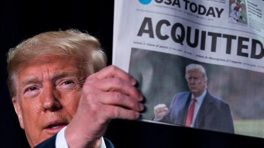 """US-Präsident Trump hält die Ausgabe der """"USA Today"""" hoch. Schlagzeile: Freigesprochen!"""