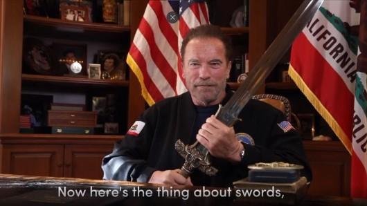 Arnold Schwarzenegger zieht in seiner Videobotschaft ein Schwert aus der Filmreihe Conan.