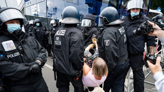 Die Polizei trägt bei der Querdenker-Demo in Berlin eine Demonstrantin weg. Obwohl es verboten war, demonstrierten Tausende.