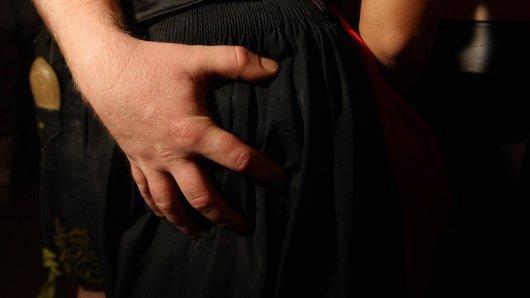 Ein Mann belästigt eine Frau sexuell.
