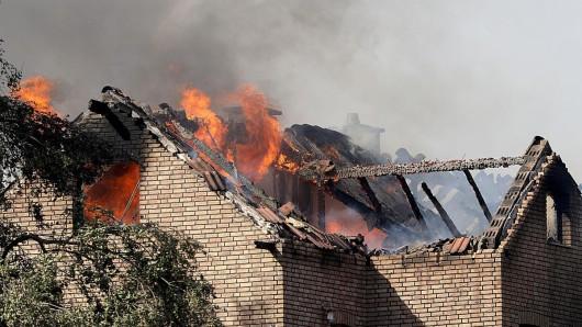 Flammen schlagen aus dem Dachstühlen brennender Häusern an der Bahnstrecke in Siegburg.