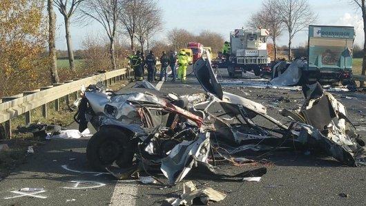 Ausgebrannt liegt ein Autowrack auf der Bundesstraße 55 bei Jülich, im Hintergrund ist ein demolierter Lastwagen zu erkennen. Bei dem Crash starben zwei Menschen, der Lkw-Fahrer wurde schwer verletzt.