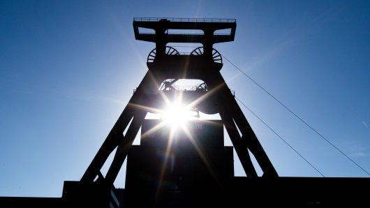 Sonne scheint durch den Förderturm der Zeche Zollverein. Viele nutzen das schöne Wetter am Wochenende für einen Spaziergang.