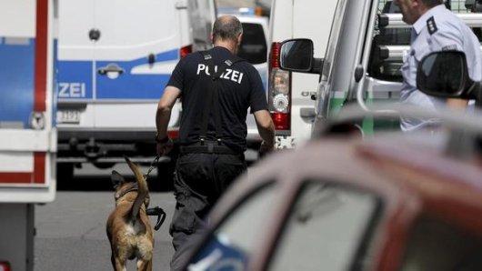 Ein Polizist geht bei den Razzien mit einem Sprengstoffspürhund zu einem Wohnhaus.
