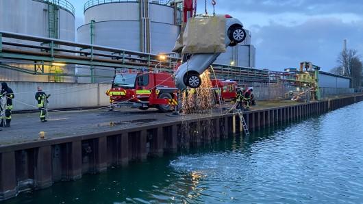 Hier wird das Auto mit einem Feuerwehrkran aus dem Wasser gehoben.