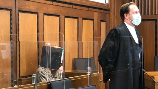 Der Angeklagte Christian R. verbirgt sein Gesicht vor den Fotografen. Vor ihm inem Verteidiger Mathias Bradler.