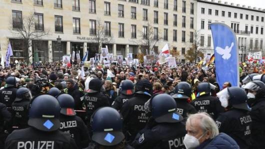 Teilnehmer einer Demonstration gegen die Corona-Einschränkungen der Bundesregierung und Polizisten stehen sich zwischen Brandenburger Tor und dem Reichstagsgebäude gegenüber.