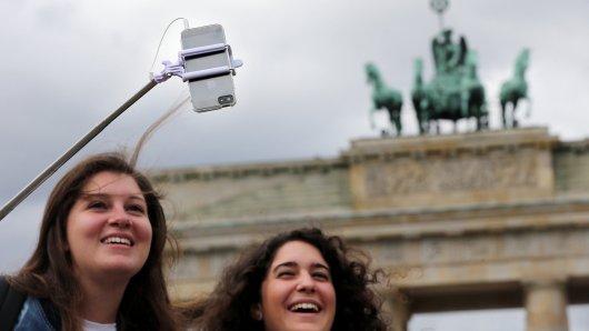 Mit einem sogenannten Selfie-Stick fotografieren sich zwei junge französische Touristinnen am 25.08.2015, bei Temperaturen um 21 Grad Celsius, vor dem Brandenburger Tor in Berlin. Die deutsche Hauptstadt ist Anziehungspunkt für Touristen aus der ganzen Welt. Foto: Wolfgang Kumm/dpa +++(c) dpa - Bildfunk+++