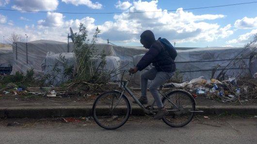 Italien, San Ferdinando:Ein Migrant fährt mit dem Fahrrad an einer Ghetto-Siedlung vorbei.