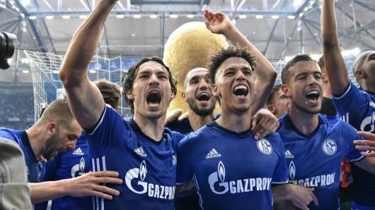 Spieler des F Schalke 04 feiern mit ihren Fans den Sieg über Borussia Dortmund.
