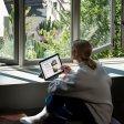 Frau sitzt am Fenster Microsoft Surface Pro