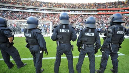 Polizisten beobachten in einem Fußballstadion Zuschauer