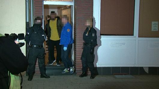 Polizisten führen einen der Verdächtigen aus einem Wohnhaus an der Duisburger Straße in Oberhausen.