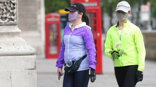 Zwei Frauen in London, beide tragen Mundschutz, um die Ausbreitung des Coronavirus zu verhindern.