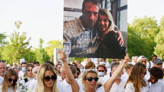 Ehefrau Veronique hält ein Foto-Plakat ihres verstorbenen Mannes hoch.