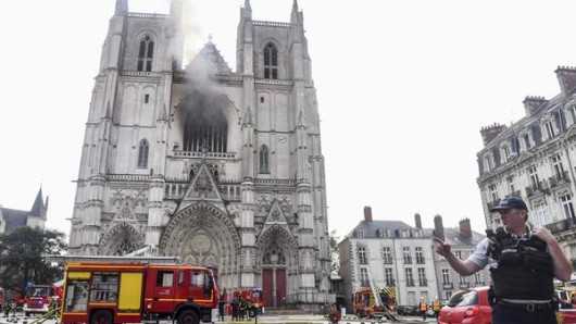 Ein französischer Polizist gestikuliert vor der Kathedrale Saint-Pierre-et-Saint-Paul. In der Kathedrale der westfranzösischen Stadt Nantes ist ein Feuer ausgebrochen.
