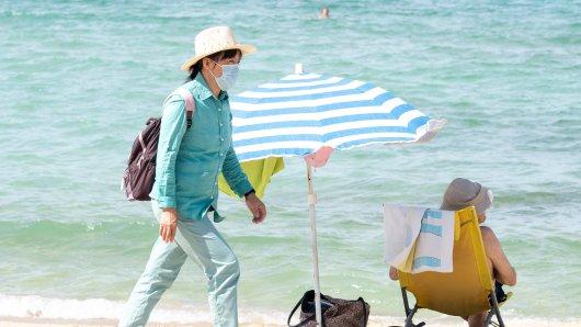 Noch machen einige Touristen Urlaub auf Mallorca und können sich einen schönen Tag am Strand machen. Doch die Inzidenzen steigen, für die Tourismusbranche wird es eng.