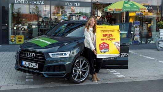 WestLotto-Annahmestellenleiterin Hildegard Kerkhoff-Kemper freut sich auf die Sonderauslosung und präsentiert vor ihrem Geschäft das Fahrzeug.