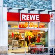 Essen, Germany - January 10, 2015: Capture of people shopping in Rewe supermarket. Winter shot through open entrance over street. People are standing in a queue at bakery. At right side a person is walking on sidewalk. Scene is in Essen Kettwig.