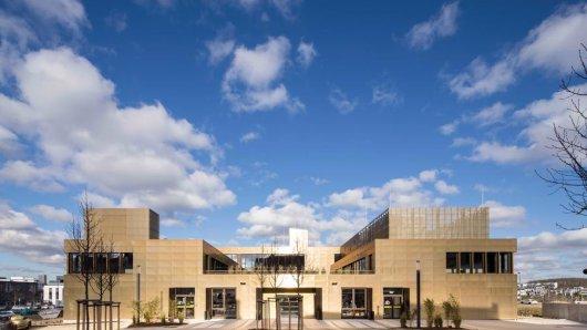 Die Rückansicht der Zentrale des Unternehmens Microsonic, die aufgrund ihrer glänzenden Fassade aus Kupfer vielen Hördern auffällt.